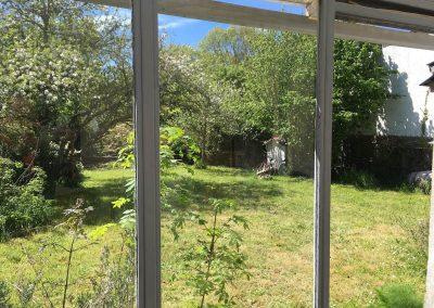 Le jardin vu de la véranda avec table de jardin et 10 fauteuils